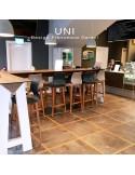 Exemple tabouret de bar UNI en situation, assise coque effet matelassé couleur, piétement bois teinté ou peint.